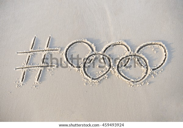 RIO DE JANEIRO - APRIL 4, 2016: Handwritten hashtag social media message for the Rio 2016 Olympics with rings drawn in smooth sand as the city prepares to host the Games.