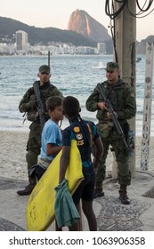 RIO DE JANEIRO - AUGUST 5 : Police officer standing guard with young local children at Copacabana beach downtown city during Olympics in Rio De Janeiro, Brazil on August 5, 2016.