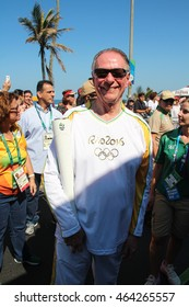 RIO DE JANEIRO, AUGUST 5, 2016: Olympic torch arrives in Ipanema beach for the Olympic Games. Carlos Arthur Nuzman, President of the Brazilian olympic committee (COB), holds the torch.