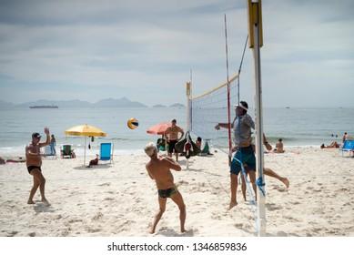 Rio de Janeiro, Brasil- March 05,2019: Men play volleyball in Copacabana. Citizens sunbathe