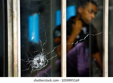 Rio de Janeiro, Brazil  08th March, 2018  A Rio de Janeiro Police agent is seen behind the glass broken by a bullet on a police facility atop the Alemao shantytown after a shooting with druglords