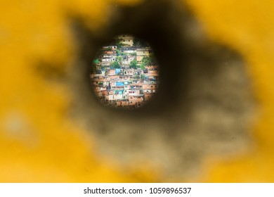 Rio de Janeiro, Brazil  08th March, 2018  The Alemao shantytown is seen through a hole on  cement blocks that surrounded a police facitlity used as protection against the bullets from druglords