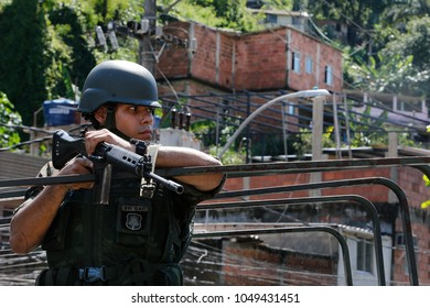 Rio de Janeiro, Brazil  16th March, 2018    A Brazilian army soldier secures the entrance of Viradouro shantytown. Army is in charge of the Rio de Janeiro security.