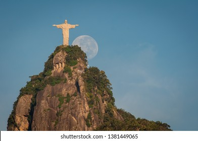 Rio de Janeiro, Brazil - April 21, 2019: Christ the Redeemer Statue on top of the Corcovado mountain and the Moon is next to it.