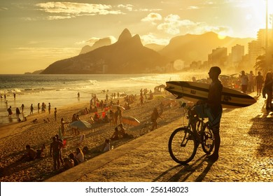 RIO DE JANEIRO, BRAZIL - APRIL 23, 2013: Silhouete of Brazilian surfer overlooking the ocean at Praia de Ipanema with Morro Dois Irmaos  and the sun setting in the background.