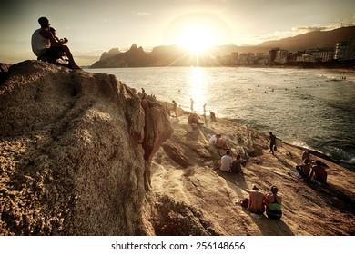 RIO DE JANEIRO, BRAZIL - APRIL 25, 2013: Brazilian boy sitting on the rock and enjoying a beautiful sunset at Praia do Arpoador.