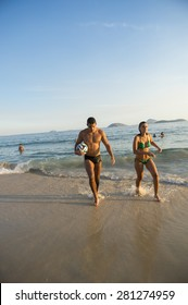 RIO DE JANEIRO, BRAZIL - APRIL 1, 2014: Young Brazilian man and woman walk with football on the shore of Ipanema Beach at Posto 9, a famous gathering place for sport and recreation.