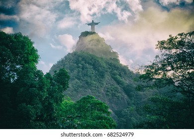 RIO DE JANEIRO, BRAZIL - APRIL 15, 2017: Christ the Redeemer on top of mountain, Rio de Janeiro, Brazil. Vintage feeling with smoke, clouds and trees. This is a truly destination for all brazilians.