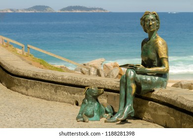 """Rio de Janeiro, Brazil - August 20, 2018: Statue of the writer Clarice Lispector with her dog in the """"Fishermen's Way"""" with the sea in the background on the beach of Leme"""