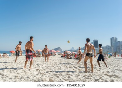 Rio de Janeiro, Brazil - August 16, 2016: Group of youngsters playing foot volley on the beach of Copacabana on a bright sunny day with blue sky with typical neighbourhood scenery in the background