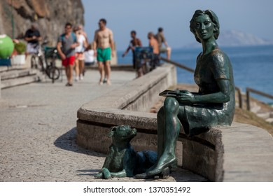 Rio de Janeiro, Brazil - August 16, 2016: Boulevard in the beach neighbourhood of Copacabana with tourists enjoying the sun and a statue of Clarice Lispector, a woman with a dog, in the foreground
