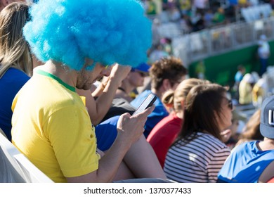 Rio de Janeiro, Brazil - August 13, 2016: Brazilian supporter with blue wig on looking at his mobile phone instead of what is going on in the stadium with crowd in the background