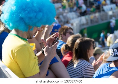 Rio de Janeiro, Brazil - August 13, 2016: Brazilian supporter with blue wig on playing with his mobile phone instead of what is going on in the stadium with crowd in the background