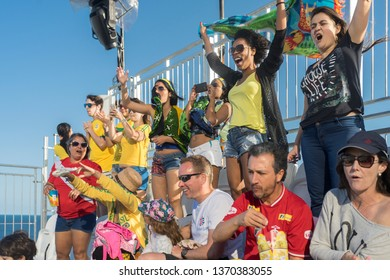 Rio de Janeiro, Brazil - August 13, 2016: A group of Brazilian supporters cheering in the top of a temporary stand on the beach of Copacabana with a blue sky in the background
