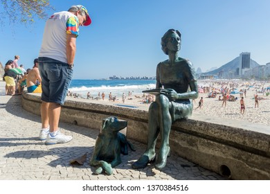 Rio de Janeiro, Brazil - August 14, 2016: Boulevard in the beach neighbourhood of Copacabana with tourist reading the text next to a statue of Clarice Lispector, a woman with a dog, in the foreground