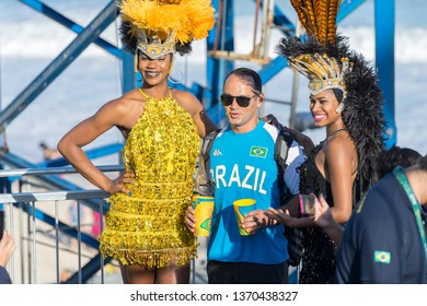 Rio de Janeiro, Brazil - August 13, 2016: Man posing with two women in Carnival outfit during the 2016 Olympic Games on a temporary stand on the beach in Copacabana with the ocean in the background