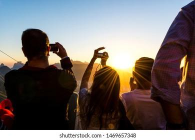 RIO DE JANEIRO, BRAZIL - AUGUST 13 2015: Tourists capture the sunset over Rio De Janeiro from Sugarloaf Mountain.