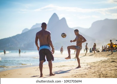 "RIO DE JANEIRO, BRAZIL - CIRCA MARCH 2018: Young Brazilians play a game of beach football keepy-uppy ""altinho"" on the shore of Ipanema Beach."