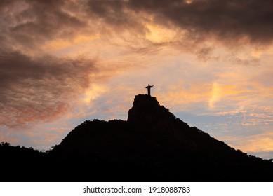 RIO DE JANEIRO, BRAZIL - FEBRUARY 3, 2021: Beautiful orange sunset clouds and Christ the Redeemer Statue mountain