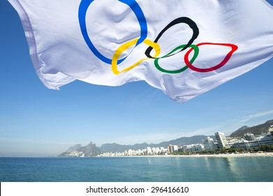RIO DE JANEIRO, BRAZIL - FEBRUARY 12, 2015: An Olympic flag flutters in the wind above the city skyline at Ipanema Beach.