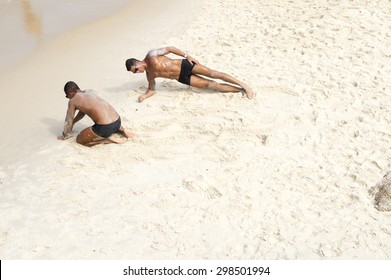 "RIO DE JANEIRO, BRAZIL - FEBRUARY 08, 2015: Pair of ""Guarda-Vidas"" lifeguards take to the sand for their morning workout at Arpoador in Ipanema Beach."