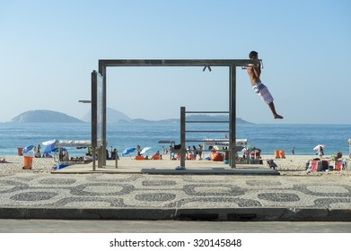 RIO DE JANEIRO, BRAZIL - FEBRUARY 22, 2015: Young man utilizes one of the many outdoor fitness stations on Ipanema Beach.