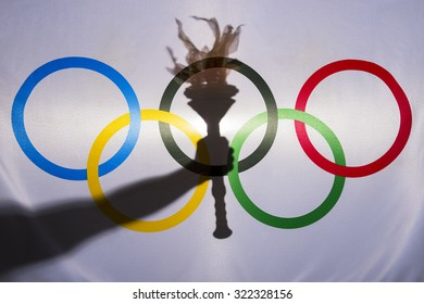 RIO DE JANEIRO, BRAZIL - FEBRUARY 3, 2015: Silhouette of hand holding sport torch behind the rings of an Olympic flag.