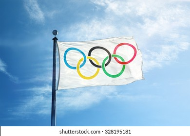 RIO DE JANEIRO, BRAZIL - FEBRUARY 12, 2015:  White Olympics Flag against the blue sky showing the rings of olympics logo. Illustrative editorial manipulation