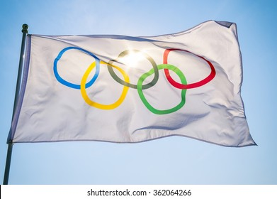 RIO DE JANEIRO, BRAZIL - FEBRUARY 12, 2015: An Olympic flag flutters in the wind backlit against bright blue sky.