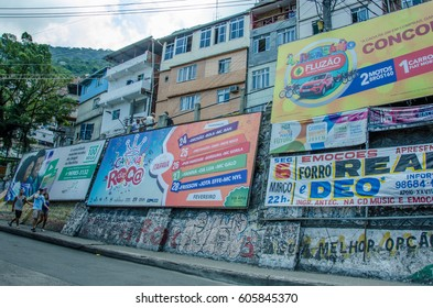 RIO DE JANEIRO, BRAZIL - FEBRUARY 28, 2017: People walk by colorful billboards along a street in the Rocinha favela advertising goods sold in their neighborhood.