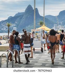 Rio de Janeiro, Brazil - Jan 6, 2018: Man checks out beautiful Afro-Brazilian woman walking down the promenade at Ipanema Beach, Rio de Janeiro, Brazil