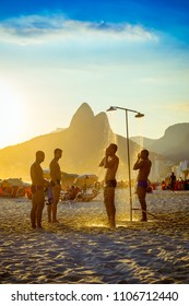 RIO DE JANEIRO, BRAZIL - JANUARY 25, 2014: Group of Brazilian men stand under the outdoor showers on Ipanema Beach at sunset.