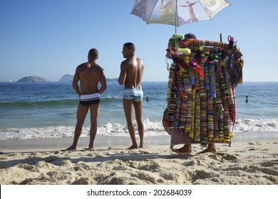 RIO DE JANEIRO, BRAZIL - JANUARY 22, 2014: Beach vendor walks past Brazililans standing on a summer day on the shore Ipanema Beach.