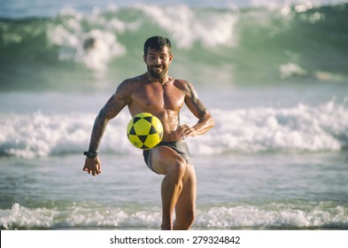 RIO DE JANEIRO, BRAZIL - JANUARY 28, 2014: Muscular young Brazilian man plays a game of altinho keepy uppy against a background of crashing waves in the Posto 9 section of Ipanema Beach.