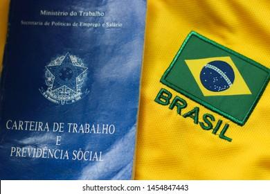 RIO DE JANEIRO, BRAZIL - JULY 18, 2019: Brazilian money (real notes) and work document and social security document (carteira de trabalho). Economy, success or crisis concept. Background Brazil shirt.