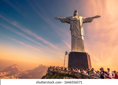 Rio de Janeiro, Brazil - July 4th 2016: Sunset at Christ the Redeemer (Cristo Redentor) with beautiful warm sky and tourists gathering at the base to enjoy views & take photos of Rio, Brazil