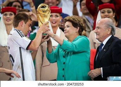RIO DE JANEIRO, BRAZIL - July 13, 2014: Brazil President, Dilma Rousseff and FIFA President Joseph Blatter handing the Cup to Lahm of Germany at Maracana Stadium. NO USE IN BRAZIL.