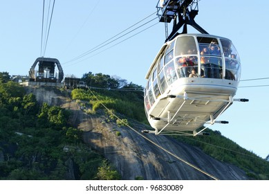 RIO DE JANEIRO, BRAZIL - JULY 16:  Tourists ride a cable car as it descends from the summit of Sugar Loaf mountain July 16, 2005 in Rio de Janeiro, Brazil.