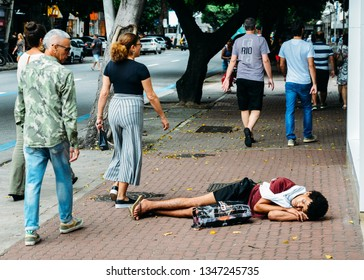 Rio de Janeiro, Brazil, March 23, 2019: Homeless young man sleeping rough while pedestrians walk next to him on busy pedestrian sidewalk in the wealthy neighbourhood of Ipanema, Rio de Janeiro, Brazil