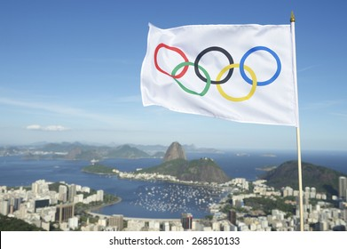RIO DE JANEIRO, BRAZIL - MARCH 05, 2015: Olympic flag waves above the city skyline view of Sugarloaf Mountain and Guanabara Bay.