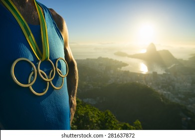 RIO DE JANEIRO, BRAZIL - MARCH 05, 2015: Athlete wearing Olympic rings gold medal above city skyline view of Sugarloaf Mountain and Guanabara Bay at sunrise.