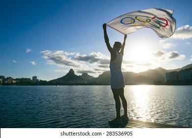 RIO DE JANEIRO, BRAZIL - MARCH 05, 2015: Athlete holds Olympic flag above sunset city skyline view of Two Brothers Mountain at Lagoa de Freitas Lagoon.