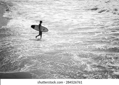 RIO DE JANEIRO, BRAZIL - MARCH 24 2015: Brazilian surfer walks into the surf at Praia do Diabo in Arpoador, near Ipanema Beach.