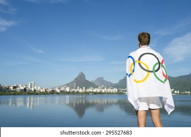 RIO DE JANEIRO, BRAZIL - MARCH 04, 2015: Man stands draped in Olympic flag in front of a skyline view of Dois Irmaos Two Brothers Mountain from Lagoa Rodrigo da Freitas Lagoon.