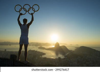RIO DE JANEIRO, BRAZIL - MARCH 05, 2015: Illustrative editorial of man standing in silhouette holding Olympic rings above city skyline view of Sugarloaf Mountain and Guanabara Bay at sunrise.