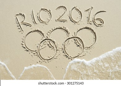 RIO DE JANEIRO, BRAZIL - MARCH 20, 2015: Wave approaches Olympic rings drawn in the sand under Rio 2016 message on Ipanema Beach in anticipation of the city hosting the 2016 Summer Games.