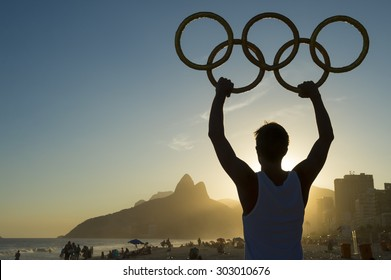 RIO DE JANEIRO, BRAZIL - MARCH 05, 2015: Athlete holding Olympic rings above sunset city skyline view of Two Brothers Mountain at Ipanema Beach.