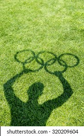 RIO DE JANEIRO, BRAZIL - MARCH 20, 2015: Shadow of a man holds Olympic rings on a green grass playing field.