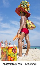 RIO DE JANEIRO, BRAZIL - MARCH 15, 2015: Brazilian beach vendor Valdemar Nascimento sells fruit salad in a recognizable hat in the flamboyant style of Carmen Miranda.