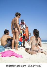 RIO DE JANEIRO, BRAZIL - MARCH 05, 2013: Vendors sell bikinis and canga beach blankets to sunbathers on Ipanema Beach.